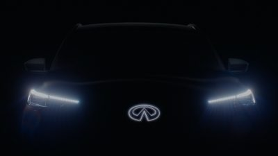 Front profile of an INFINITI QX60 Monograph in the dark with the headlights and INFINITI badge brightly lit.