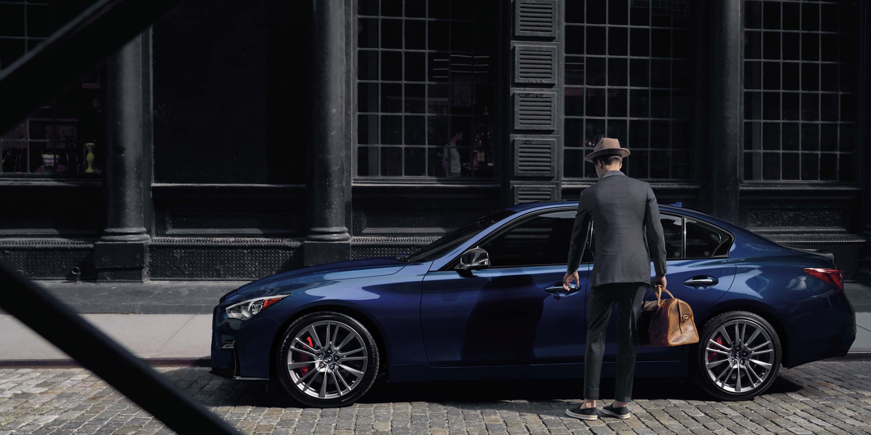 Man walking up to a luxurious Irdium blue INFINITI Q50 sedan