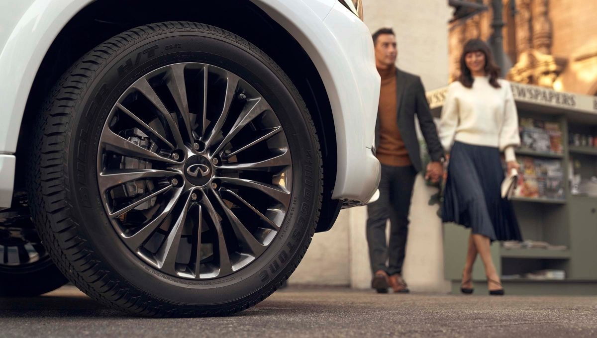 man and woman approaching a white INFINITI vehicle