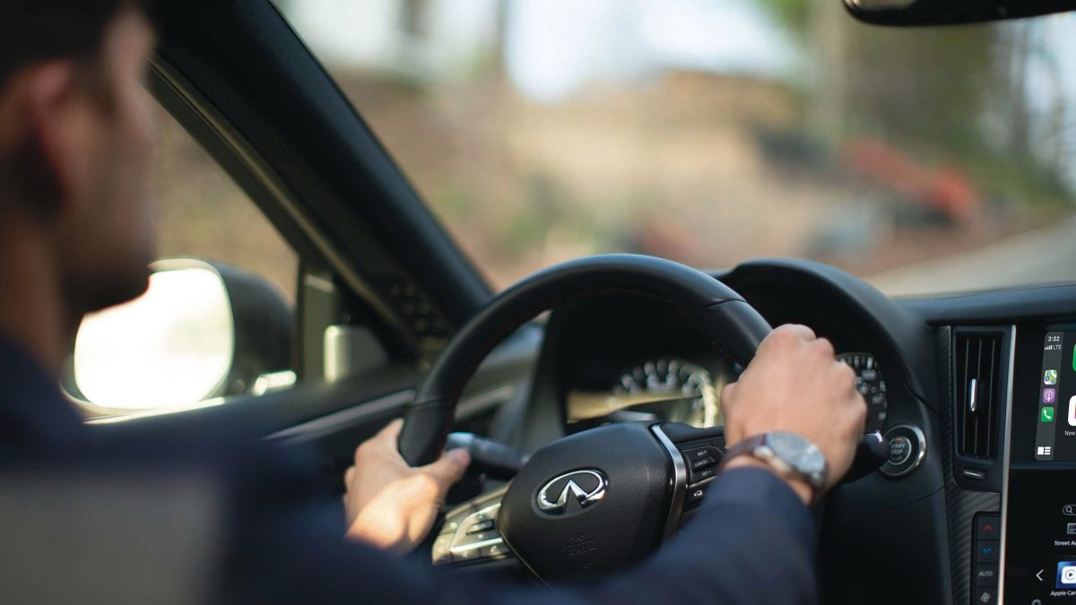 man holding the steering wheel as he drives an INFINITI car