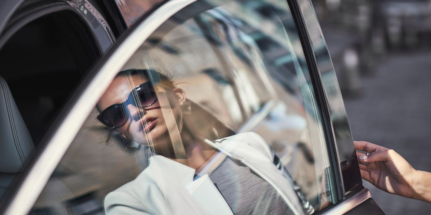 A womans reflection on the window of an INFINITI car