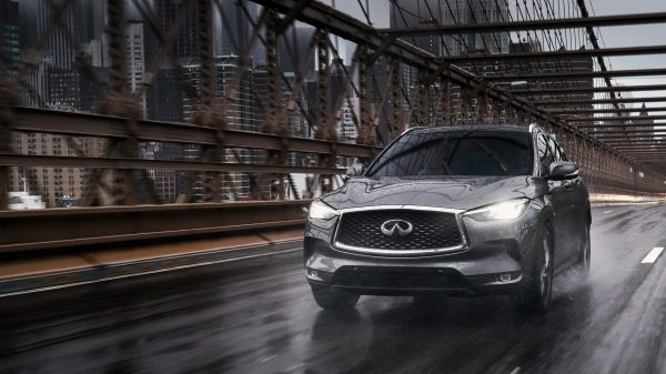 2020 INFINITI QX50 Luxury Crossover Driving Along An Urban Road At Dusk