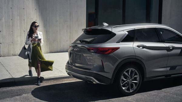 A woman walking towards a parked 2021 INFINITI QX50 crossover as she start her vehicle prior to entering thanks to the available remote engine start system