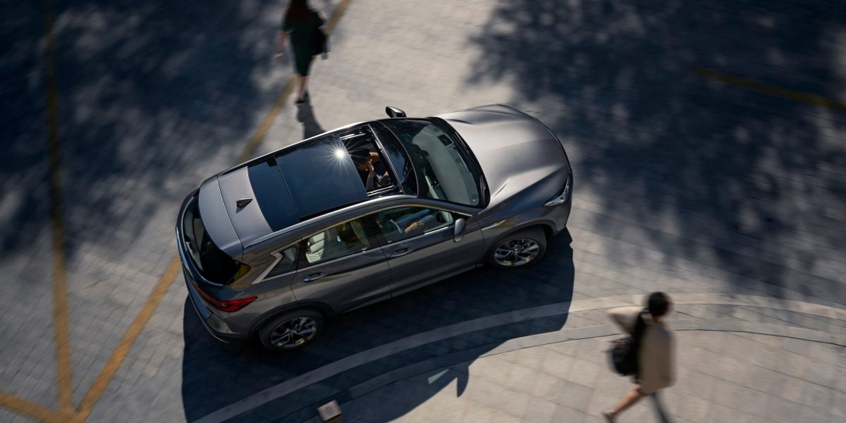 INFINITI QX50 from above with people walking passed